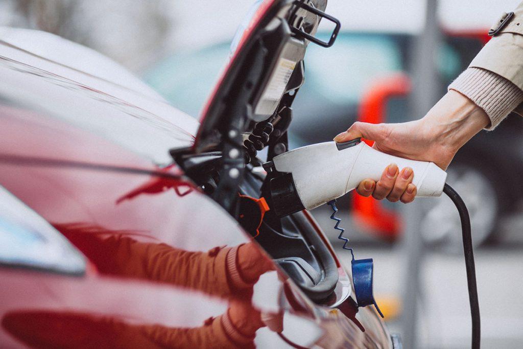 mujer cargando coche electrico